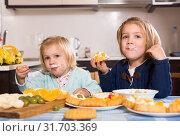 Купить «Children eat cakes at kitchen», фото № 31703369, снято 21 сентября 2019 г. (c) Яков Филимонов / Фотобанк Лори
