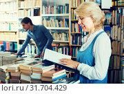 Купить «mature woman with book among bookshelves», фото № 31704429, снято 16 июня 2020 г. (c) Яков Филимонов / Фотобанк Лори