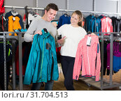 Купить «Young couple in sports shop choosing sport clothes», фото № 31704513, снято 25 октября 2017 г. (c) Яков Филимонов / Фотобанк Лори