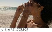 Купить «Woman wearing sunglasses on the beach 4k», видеоролик № 31705969, снято 8 февраля 2019 г. (c) Wavebreak Media / Фотобанк Лори