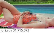 Купить «Woman in swimwear relaxing near poolside in the backyard 4k», видеоролик № 31715073, снято 12 марта 2019 г. (c) Wavebreak Media / Фотобанк Лори