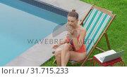 Купить «Woman in swimming costume drinking wine near swimming pool 4k», видеоролик № 31715233, снято 12 марта 2019 г. (c) Wavebreak Media / Фотобанк Лори