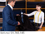 Купить «Chinese woman seller helping shopper choose clothes in store», фото № 31765145, снято 8 декабря 2019 г. (c) Яков Филимонов / Фотобанк Лори