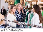 Купить «Three young emotional women friends talking in clothes shop», фото № 31765457, снято 15 марта 2018 г. (c) Яков Филимонов / Фотобанк Лори