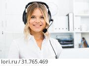 Young call center employee in headphones is sitting near laptop in the office. Стоковое фото, фотограф Яков Филимонов / Фотобанк Лори
