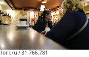 Купить «The woman is putting the cup and the glass on the bar counter at the cafe», видеоролик № 31766781, снято 12 марта 2019 г. (c) Aleksandr Sulimov / Фотобанк Лори
