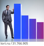 Businessman standing next to bar chart in business concept. Стоковое фото, фотограф Elnur / Фотобанк Лори