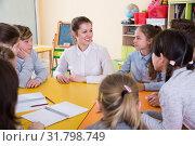 Купить «Smiling schoolboys and schoolgirls with teacher sitting», фото № 31798749, снято 28 января 2018 г. (c) Яков Филимонов / Фотобанк Лори