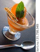 Купить «Tasty cold orange ice cream served at glass cup with wafer and mint», фото № 31798949, снято 25 августа 2019 г. (c) Яков Филимонов / Фотобанк Лори