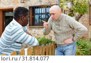 Купить «Disgruntled men talking in backyard», фото № 31814077, снято 15 декабря 2018 г. (c) Яков Филимонов / Фотобанк Лори