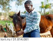 Купить «Farmworker carrying horse», фото № 31814081, снято 15 декабря 2018 г. (c) Яков Филимонов / Фотобанк Лори