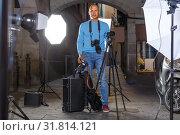 Купить «Portrait of cheerful photographer with his camera during photo shooting on town street», фото № 31814121, снято 5 октября 2018 г. (c) Яков Филимонов / Фотобанк Лори