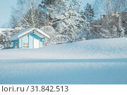 Winter landscape toned in blue. Drifts of snow sparkling in the sun against a blurred background of a small house and trees covered with snow. Shallow depth of field. Стоковое фото, фотограф Юлия Бабкина / Фотобанк Лори
