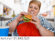 Купить «Fat woman eating fastfood in mall food court», фото № 31843521, снято 24 мая 2019 г. (c) Tryapitsyn Sergiy / Фотобанк Лори