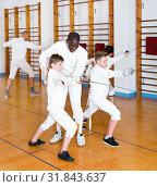 Купить «Focused boys fencers attentively listening to professional fencing coach in gym», фото № 31843637, снято 30 мая 2018 г. (c) Яков Филимонов / Фотобанк Лори