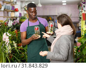 Купить «Seller offering gift flower arrangement to female», фото № 31843829, снято 14 февраля 2019 г. (c) Яков Филимонов / Фотобанк Лори