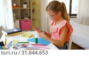 Купить «girl cutting color paper with scissors at home», видеоролик № 31844653, снято 21 июля 2019 г. (c) Syda Productions / Фотобанк Лори