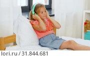 Купить «girl in headphones listening to music on cellphone», видеоролик № 31844681, снято 21 июля 2019 г. (c) Syda Productions / Фотобанк Лори