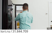 man taking food container from fridge at kitchen. Стоковая анимация, видеограф Syda Productions / Фотобанк Лори