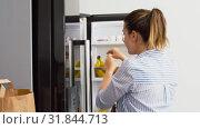 Купить «woman putting new purchased food to home fridge», видеоролик № 31844713, снято 21 июля 2019 г. (c) Syda Productions / Фотобанк Лори