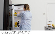Купить «woman taking apple from fridge at home kitchen», видеоролик № 31844717, снято 21 июля 2019 г. (c) Syda Productions / Фотобанк Лори