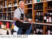 Купить «Positive male vintner holding out bottle of wine», фото № 31845237, снято 8 мая 2019 г. (c) Яков Филимонов / Фотобанк Лори