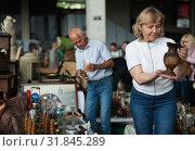 Smiling mature spouses buying retro handicrafts on flea market. Стоковое фото, фотограф Яков Филимонов / Фотобанк Лори