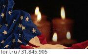 Digital animation of crumpled American flag against lit candles 4k. Стоковое видео, агентство Wavebreak Media / Фотобанк Лори