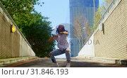 Купить «Young dancer practicing dance on asphalt road in the city 4k», видеоролик № 31846193, снято 26 сентября 2018 г. (c) Wavebreak Media / Фотобанк Лори