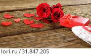 Купить «Red roses, gift box and heart shapes on the wooden surface 4k», видеоролик № 31847205, снято 11 октября 2018 г. (c) Wavebreak Media / Фотобанк Лори