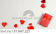 Купить «Red gift box and red hearts on white surface 4k», видеоролик № 31847221, снято 11 октября 2018 г. (c) Wavebreak Media / Фотобанк Лори