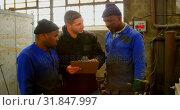 Купить «Workers discussing with supervisor on clipboard in workshop 4k», видеоролик № 31847997, снято 27 сентября 2018 г. (c) Wavebreak Media / Фотобанк Лори