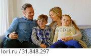 Купить «Front view of Caucasian family sitting on the couch and watching television in a comfortable home 4k», видеоролик № 31848297, снято 6 ноября 2018 г. (c) Wavebreak Media / Фотобанк Лори
