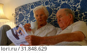 Купить «Front view of Caucasian senior couple reading news paper on bed in bedroom at comfortable home 4k», видеоролик № 31848629, снято 6 ноября 2018 г. (c) Wavebreak Media / Фотобанк Лори