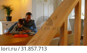 Купить «Front view of young Caucasian father helping son with homework in a comfortable home 4k», видеоролик № 31857713, снято 6 ноября 2018 г. (c) Wavebreak Media / Фотобанк Лори