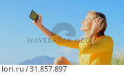 Side view of young Caucasian woman taking selfie with mobile phone 4k. Стоковое видео, агентство Wavebreak Media / Фотобанк Лори
