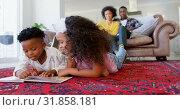 Купить «Front view of cute black kids reading story book in living room at comfortable home 4k», видеоролик № 31858181, снято 7 ноября 2018 г. (c) Wavebreak Media / Фотобанк Лори