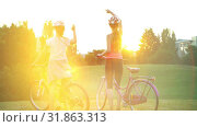 Купить «Children in helmet on bicycle rising sun salute in summer park», видеоролик № 31863313, снято 24 июля 2019 г. (c) Gennadiy Poznyakov / Фотобанк Лори