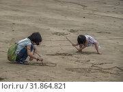 Children draw pictures on the beach, Telok Melano , Sematan, Sarawak, Malaysia (2019 год). Редакционное фото, фотограф Chua Wee Boo / age Fotostock / Фотобанк Лори