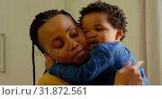 Купить «Front view of cute little black baby boy embracing his mother in a comfortable home 4k», видеоролик № 31872561, снято 19 октября 2018 г. (c) Wavebreak Media / Фотобанк Лори