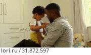 Купить «Side view of young black father playing with son on floor in a comfortable home 4k», видеоролик № 31872597, снято 19 октября 2018 г. (c) Wavebreak Media / Фотобанк Лори