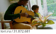 Side view of young black father and little son playing guitar in living room of comfortable home 4k. Стоковое видео, агентство Wavebreak Media / Фотобанк Лори