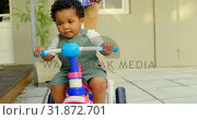 Купить «Front view of cute little black boy riding on tricycle in back yard of their home 4k», видеоролик № 31872701, снято 19 октября 2018 г. (c) Wavebreak Media / Фотобанк Лори