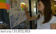 Купить «Side view of young caucasian businesswoman planning and working on glass wall of modern office 4k», видеоролик № 31872953, снято 13 октября 2018 г. (c) Wavebreak Media / Фотобанк Лори