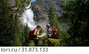 Купить «Front view of young caucasian hiker couple with backpack looking map in the dense forest 4k», видеоролик № 31873133, снято 16 июля 2018 г. (c) Wavebreak Media / Фотобанк Лори
