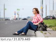 Купить «Mature woman in eyeglasses sitting on road curb and hitchhiking, waiting the car», фото № 31879449, снято 21 июня 2019 г. (c) Кекяляйнен Андрей / Фотобанк Лори