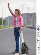 Купить «Mature woman waving hand for stop the car, standing in the middle of urban road», фото № 31879465, снято 21 июня 2019 г. (c) Кекяляйнен Андрей / Фотобанк Лори