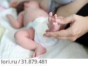 Купить «Женщина кормит грудью младенца и держит его за ножку», фото № 31879481, снято 16 июня 2019 г. (c) Кекяляйнен Андрей / Фотобанк Лори
