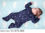 Купить «One month old infant sleeping in bed with hands up, dark blue clothes, light blue linen with clouds, full length», фото № 31879489, снято 22 июня 2019 г. (c) Кекяляйнен Андрей / Фотобанк Лори