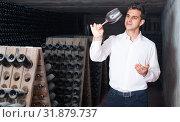 Купить «man holding glass with wine in cellar», фото № 31879737, снято 21 сентября 2016 г. (c) Яков Филимонов / Фотобанк Лори